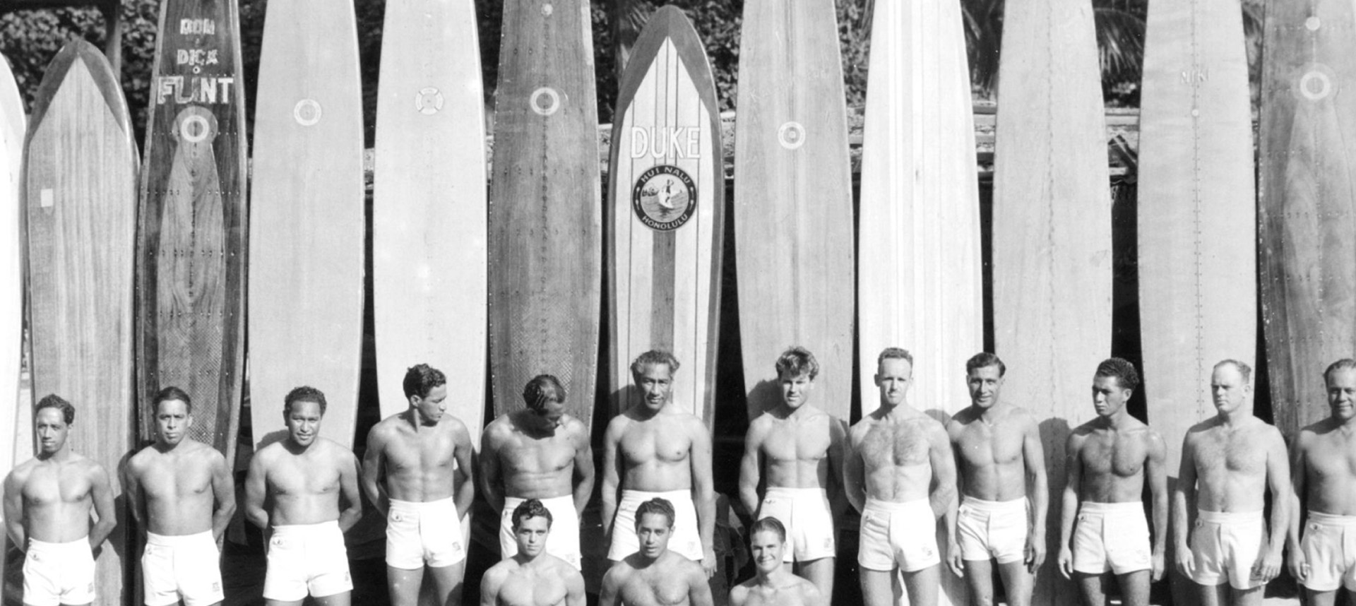 Duke and other men lined up next to surfboards