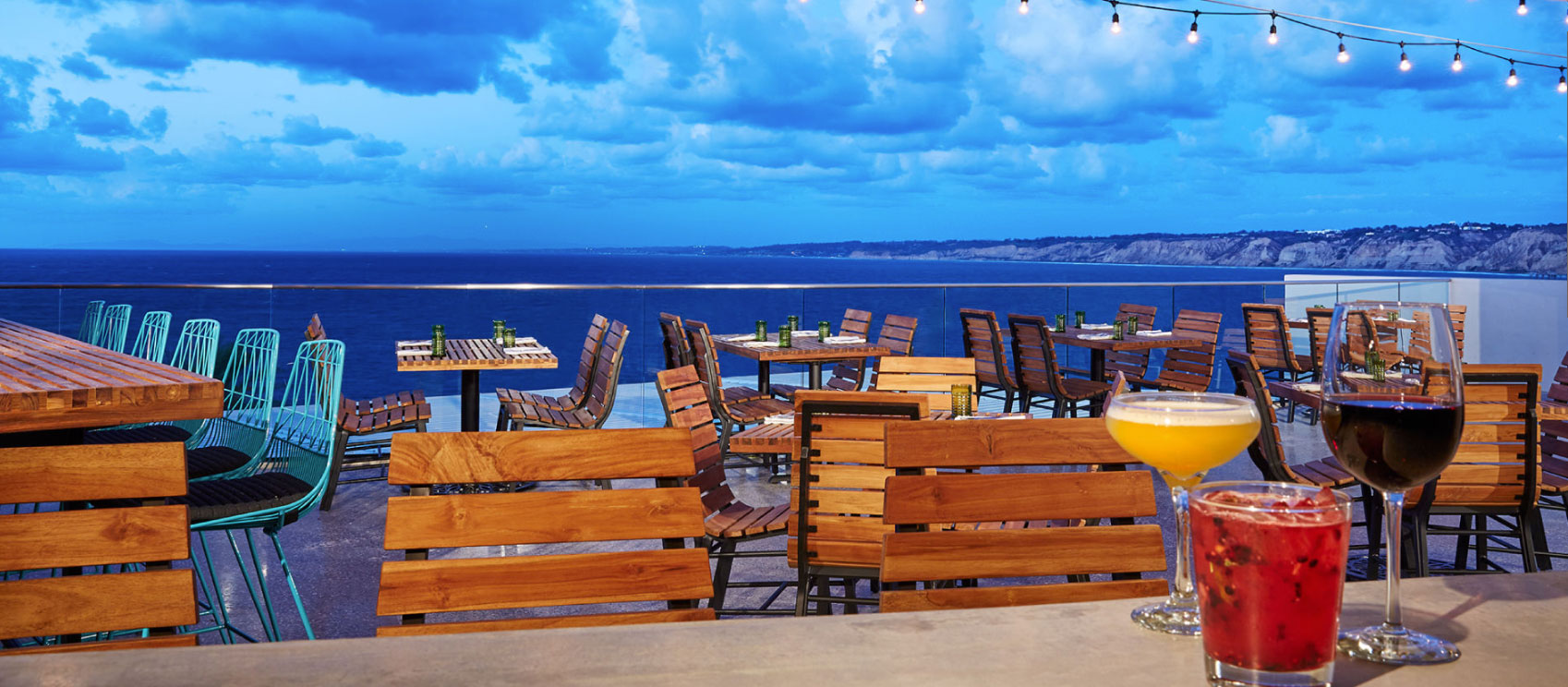 Ocean scenery with outdoor seating and three cocktails
