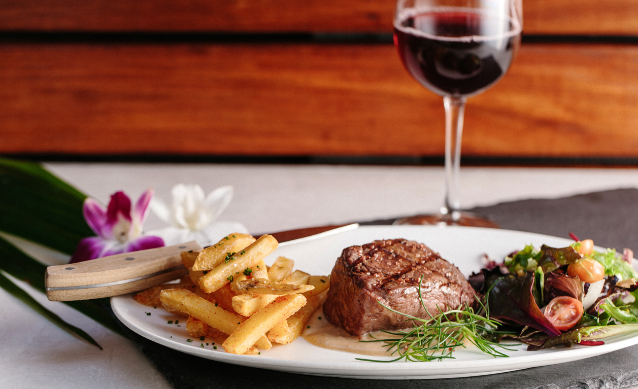 Steak, fries, and salad with wine
