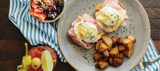 Plated eegs Benedict with an acai bowl and bloody mary